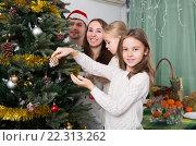Купить «Family decorating Christmas tree at home», фото № 22313262, снято 24 февраля 2018 г. (c) Яков Филимонов / Фотобанк Лори