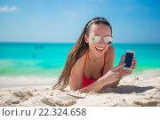 Купить «Веселая красивая девушка со смартфоном на пляже», фото № 22324658, снято 6 апреля 2014 г. (c) Дмитрий Травников / Фотобанк Лори