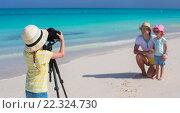 Купить «Маленькая девочка фотографирует семью на пляже», фото № 22324730, снято 8 апреля 2014 г. (c) Дмитрий Травников / Фотобанк Лори