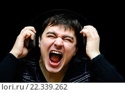 Темноволосый мужчина в наушниках громко поет на темном фоне. Стоковое фото, фотограф Анна Кирьякова / Фотобанк Лори