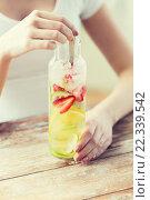 Купить «close up of woman with fruit water in glass bottle», фото № 22339542, снято 28 апреля 2015 г. (c) Syda Productions / Фотобанк Лори