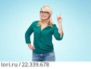 Купить «young woman with eyeglasses pointing finger up», фото № 22339678, снято 7 февраля 2016 г. (c) Syda Productions / Фотобанк Лори