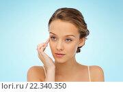 Купить «young woman applying cream to her face», фото № 22340350, снято 31 октября 2015 г. (c) Syda Productions / Фотобанк Лори
