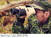 Купить «young soldier or hunter with binocular in forest», фото № 22355574, снято 14 августа 2014 г. (c) Syda Productions / Фотобанк Лори