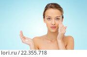 Купить «young woman applying cream to her face», фото № 22355718, снято 31 октября 2015 г. (c) Syda Productions / Фотобанк Лори