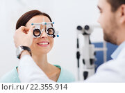 Купить «optician with trial frame and patient at clinic», фото № 22355914, снято 25 ноября 2015 г. (c) Syda Productions / Фотобанк Лори