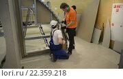 Купить «Молодые работники выполняет задачу с гипсокартоном», видеоролик № 22359218, снято 24 марта 2016 г. (c) Сергей Буторин / Фотобанк Лори