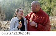 Купить «Handsome man and cheerful woman eating sandwitches at picnic outdoors», видеоролик № 22362618, снято 5 февраля 2016 г. (c) Яков Филимонов / Фотобанк Лори