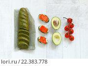 Вид сверху на багет со шпинатом, авокадо, томатами черри и бутерброды с красной рыбой. Стоковое фото, фотограф Козлова Анастасия / Фотобанк Лори