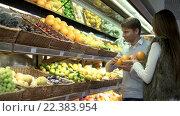 Купить «Young couple choosing fruits in store», видеоролик № 22383954, снято 25 марта 2016 г. (c) Raev Denis / Фотобанк Лори