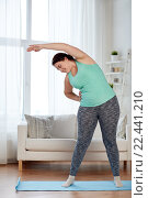 plus size woman exercising on mat at home. Стоковое фото, фотограф Syda Productions / Фотобанк Лори