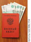 Купить «Военный билет с деньгами лежит на столе», фото № 22506114, снято 20 ноября 2015 г. (c) Денис Ларкин / Фотобанк Лори