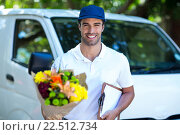 Купить «Smiling delivery man holding flower bouquet and clipboard», фото № 22512734, снято 10 декабря 2015 г. (c) Wavebreak Media / Фотобанк Лори