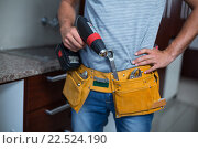 Купить «Midsection of man holding cordless hand drill», фото № 22524190, снято 10 декабря 2015 г. (c) Wavebreak Media / Фотобанк Лори