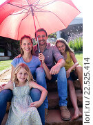 Купить «Happy family sitting in garden under a red umbrella», фото № 22525414, снято 29 ноября 2015 г. (c) Wavebreak Media / Фотобанк Лори