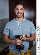 Купить «Portrait of cheerful man holding cordless hand drill», фото № 22526534, снято 10 декабря 2015 г. (c) Wavebreak Media / Фотобанк Лори
