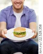 Купить «close up of man holding hamburger on plate at home», фото № 22528358, снято 22 марта 2014 г. (c) Syda Productions / Фотобанк Лори