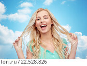 Купить «smiling young woman holding her strand of hair», фото № 22528826, снято 13 февраля 2016 г. (c) Syda Productions / Фотобанк Лори