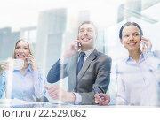 Купить «business team with smartphones having conversation», фото № 22529062, снято 9 ноября 2013 г. (c) Syda Productions / Фотобанк Лори