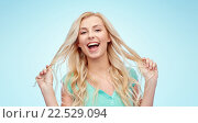 smiling young woman holding her strand of hair. Стоковое фото, фотограф Syda Productions / Фотобанк Лори