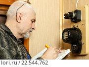Купить «Пенсионер снимает показания электросчетчика», фото № 22544762, снято 31 марта 2016 г. (c) Акиньшин Владимир / Фотобанк Лори