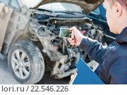 Купить «Insurance agent photographing car damage for claim form», фото № 22546226, снято 15 марта 2016 г. (c) Дмитрий Калиновский / Фотобанк Лори