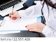 Купить «Доктор с красным маникюром пишет заметки», фото № 22551426, снято 28 декабря 2014 г. (c) Ирина Мойсеева / Фотобанк Лори