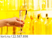 Купить «Рука с бокалом шампанского на желтом фоне», фото № 22587898, снято 10 января 2016 г. (c) Сергей Новиков / Фотобанк Лори