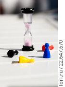 Разноцветные фишки и песочные часы на деревянном столе. Стоковое фото, фотограф Анна Кирьякова / Фотобанк Лори
