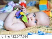 Малыш с игрушками лежит на одеяле. Стоковое фото, фотограф Анна Кирьякова / Фотобанк Лори