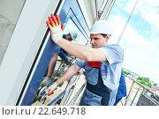 Купить «builders worker installing glass windows on facade», фото № 22649718, снято 29 июня 2015 г. (c) Дмитрий Калиновский / Фотобанк Лори