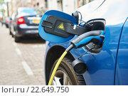 Купить «power supply plugged into an electric car during charging», фото № 22649750, снято 27 апреля 2015 г. (c) Дмитрий Калиновский / Фотобанк Лори