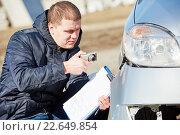 Купить «Insurance agent photographing car damage for claim form», фото № 22649854, снято 15 марта 2016 г. (c) Дмитрий Калиновский / Фотобанк Лори