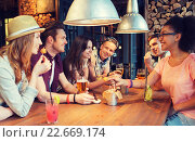 happy friends with drinks talking at bar or pub. Стоковое фото, фотограф Syda Productions / Фотобанк Лори