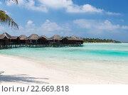 Купить «bungalow huts in sea water on exotic resort beach», фото № 22669818, снято 13 февраля 2016 г. (c) Syda Productions / Фотобанк Лори