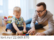 Купить «father and son playing with toy blocks at home», фото № 22669870, снято 19 марта 2016 г. (c) Syda Productions / Фотобанк Лори