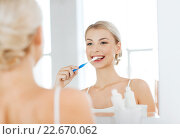 woman with toothbrush cleaning teeth at bathroom. Стоковое фото, фотограф Syda Productions / Фотобанк Лори