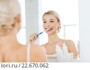 Купить «woman with toothbrush cleaning teeth at bathroom», фото № 22670062, снято 13 февраля 2016 г. (c) Syda Productions / Фотобанк Лори