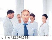 Купить «businessman in office with group on the back», фото № 22670594, снято 9 июня 2013 г. (c) Syda Productions / Фотобанк Лори