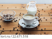 Купить «close up coffee cup and grains on wooden table», фото № 22671518, снято 7 апреля 2016 г. (c) Syda Productions / Фотобанк Лори