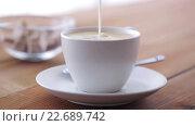 Купить «cream pouring to coffee cup on wooden table», видеоролик № 22689742, снято 15 апреля 2016 г. (c) Syda Productions / Фотобанк Лори