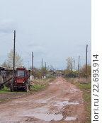 Купить «Деревенская улица (грязь, лужи). Красный трактор на обочине.», фото № 22693914, снято 23 апреля 2016 г. (c) Нина Карымова / Фотобанк Лори