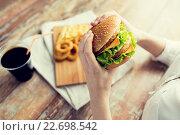 Купить «close up of woman hands holding hamburger», фото № 22698542, снято 21 мая 2015 г. (c) Syda Productions / Фотобанк Лори