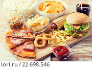 Купить «close up of fast food snacks and drink on table», фото № 22698546, снято 21 мая 2015 г. (c) Syda Productions / Фотобанк Лори