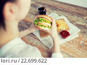 Купить «close up of woman hands holding hamburger», фото № 22699622, снято 21 мая 2015 г. (c) Syda Productions / Фотобанк Лори