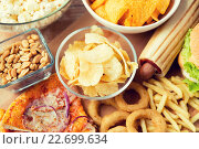 Купить «close up of fast food snacks and drink on table», фото № 22699634, снято 21 мая 2015 г. (c) Syda Productions / Фотобанк Лори