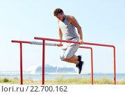 Купить «young man exercising on parallel bars outdoors», фото № 22700162, снято 25 августа 2015 г. (c) Syda Productions / Фотобанк Лори