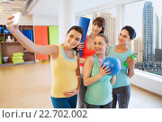 pregnant women taking selfie by smartphone in gym. Стоковое фото, фотограф Syda Productions / Фотобанк Лори