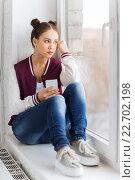Купить «teenage girl sitting on windowsill with smartphone», фото № 22702198, снято 19 декабря 2015 г. (c) Syda Productions / Фотобанк Лори