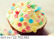Купить «close up of glazed cupcake or muffin on table», фото № 22702682, снято 21 мая 2015 г. (c) Syda Productions / Фотобанк Лори